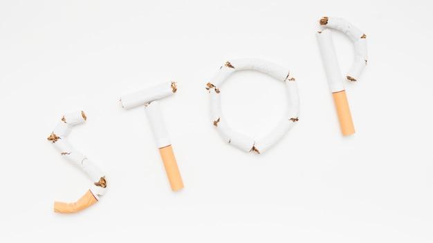 Conceito de parar de fumar feito de cigarro contra o pano de fundo branco