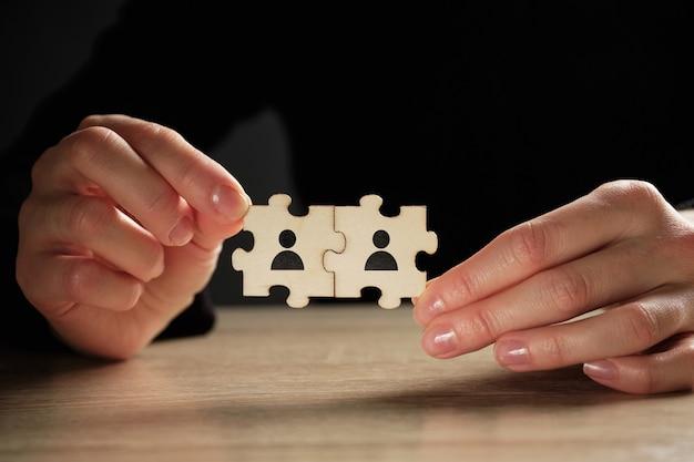 Conceito de parceria do quebra-cabeça de pessoas abstratas nas mãos.