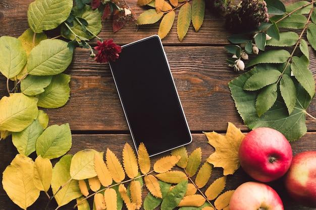 Conceito de parede de madeira de folhas de outono de comércio eletrônico. tecnologia de smartphone.
