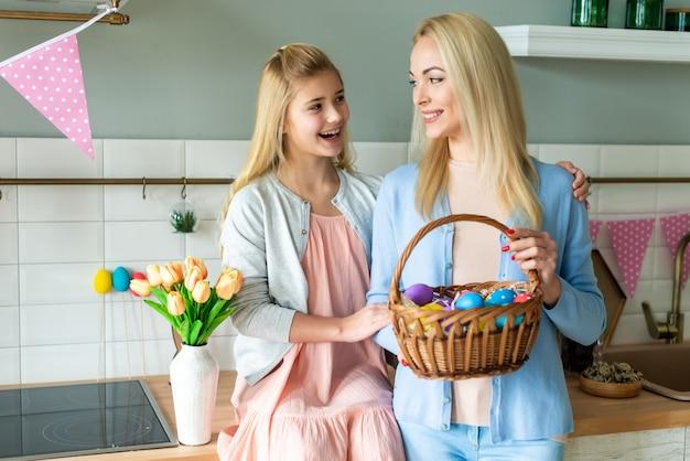Conceito de páscoa, a mãe tem uma cesta de páscoa e sabão com a filha.