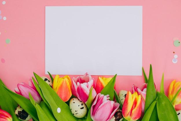Conceito de páscoa, branco em branco e confetes, tulipas multicoloridas, ovos de codorna em fundo rosa