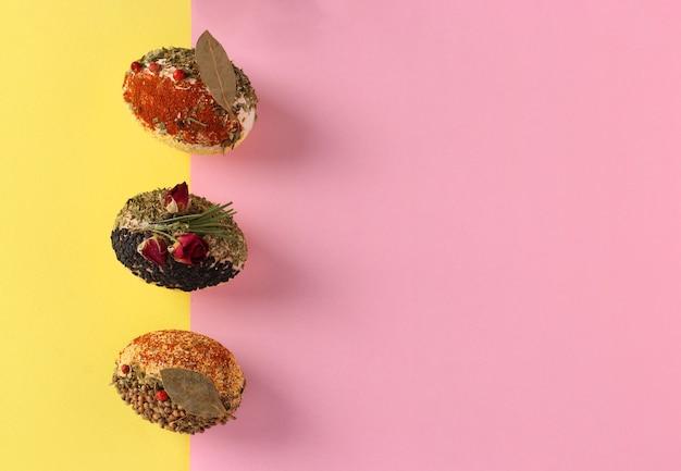 Conceito de páscoa com ovos decorados com diferentes especiarias e cereais sem corantes e conservantes em fundo rosa e amarelo, espaço para texto