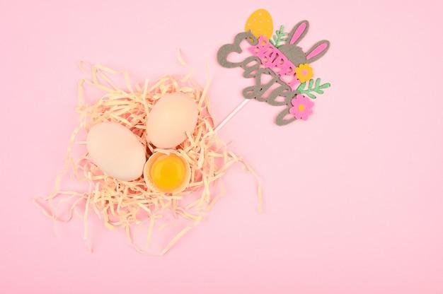 Conceito de páscoa em um fundo rosa. ovo em uma colher de pau. uma bandeja de ovos em um fundo branco e rosa. bandeja ecológica com testículos. tendência minimalista, vista superior. bandeja de ovos. conceito de páscoa