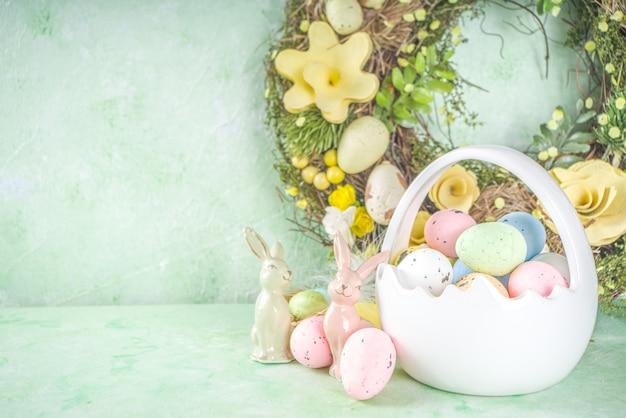 Conceito de páscoa feliz com ovos de páscoa na cesta e flores da primavera. fundo de páscoa com espaço de cópia e moldura