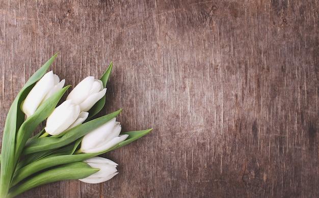 Conceito de páscoa - flores (tulipas brancas) sobre fundo de madeira rústica