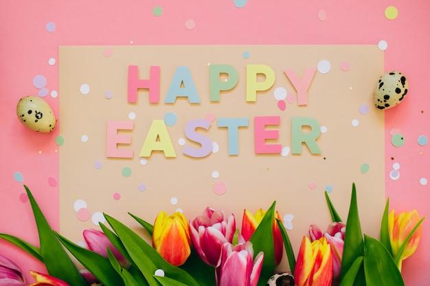 Conceito de páscoa. o papel feliz de easter cortou a inscrição com as tulipas cor-de-rosa e vermelhas e os ovos de codorniz no fundo cor-de-rosa. copie o espaço, lay plana.