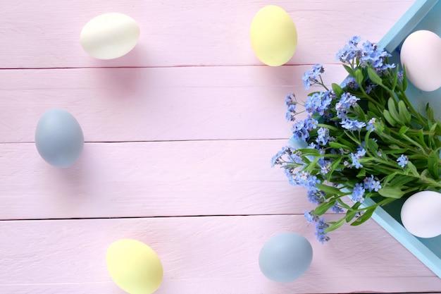 Conceito de páscoa ovos de páscoa de cores pastel, flores miosótis em uma bandeja suavemente azul e diário vazio em um fundo rosa placa de madeira.