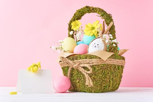 Conceito de páscoa. ovos de páscoa na cesta decorativa com flores em um fundo rosa