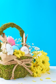 Conceito de páscoa. ovos no cesto decorado com flores sobre fundo azul