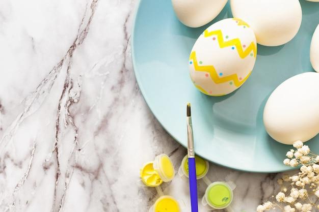 Conceito de páscoa - postura plana de placa azul com ovos e tintas coloridas com um pincel para ovos de pintura tradicional em uma mesa de mármore