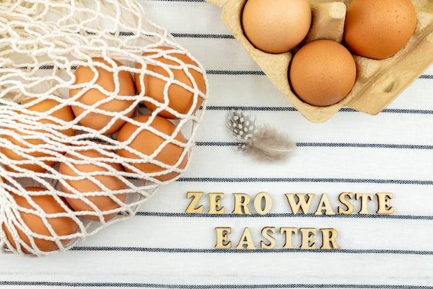 Conceito de páscoa zero desperdício. nenhum conceito de saco plástico. estilo mínimo. saco de compra de malha bege com ovos de galinha marrons em fundo de matéria têxtil.