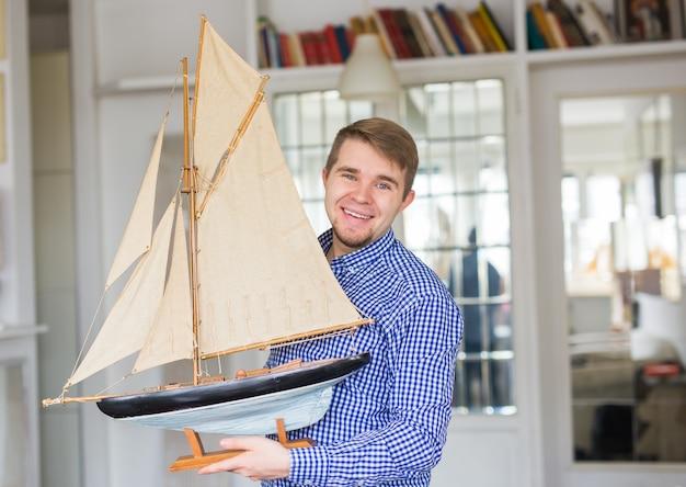 Conceito de passatempo, coleta, navio e pessoas - homem bonito segurando o layout de um veleiro
