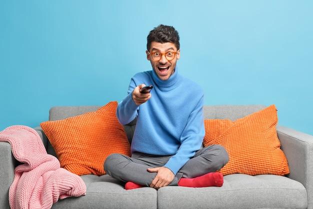 Conceito de passatempo de lazer de pessoas. homem adulto com a barba por fazer radiante sentado em pose de lótus no sofá, segurando o controle remoto e assistindo a um programa engraçado na televisão