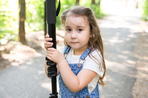 Conceito de passatempo, profissão, filhos e fotógrafo - criança com câmera na floresta