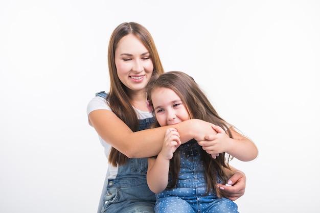 Conceito de paternidade, família e filhos - um retrato de uma mãe e sua filha se divertindo e sorrindo sobre uma superfície branca