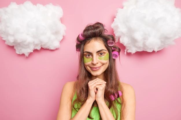 Conceito de penteado de tempo de beleza de pessoas. mulher morena satisfeita aplica adesivos de colágeno verde sob os olhos para reduzir o inchaço, mantém as mãos juntas sob o queixo em poses internas contra a parede rosada do estúdio