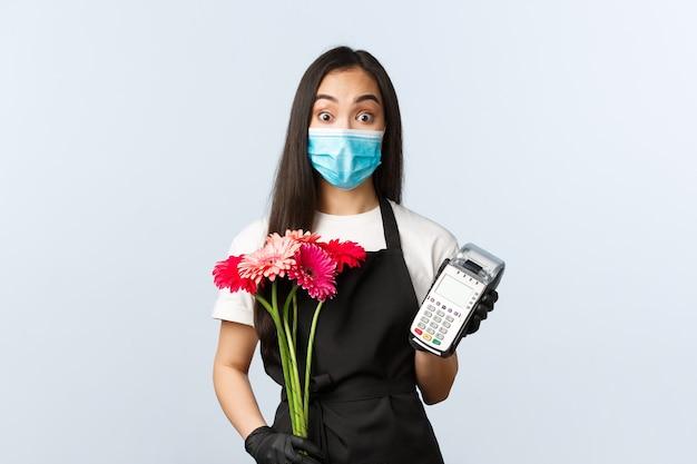 Conceito de pequenas empresas, pandemia de coronavírus, pedidos e lojas. animado jovem funcionário da loja, florista com máscara médica, segurando o buquê e o terminal de pdv, visitante fazendo compra sem contato.
