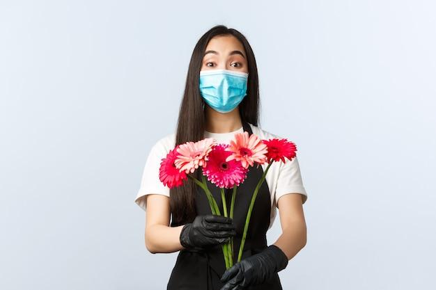 Conceito de pequenas empresas, pandemia de coronavírus, pedidos e lojas. entusiasta e fofa funcionária asiática, proprietária de uma floricultura usando máscara médica e luvas para dar buquê ao cliente