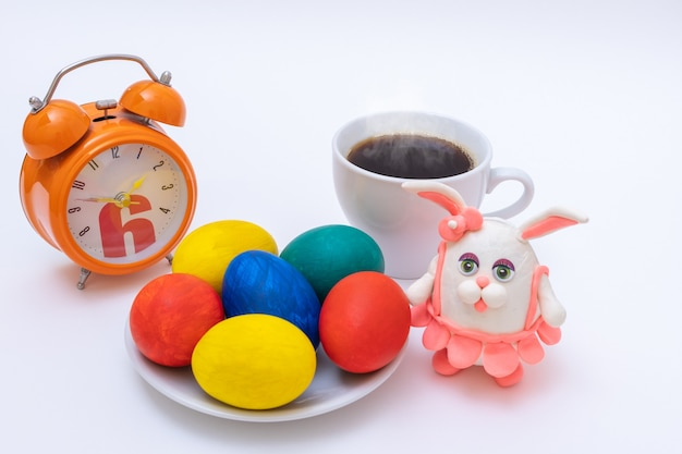 Conceito de pequeno-almoço de páscoa. ovos de páscoa pintados à mão, caneca com café ou chocolate quente, despertador e coelhinho da páscoa caseiro. conceito de feliz páscoa.