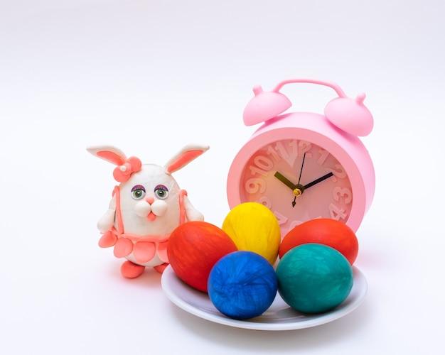 Conceito de pequeno-almoço de páscoa. ovos de páscoa pintados à mão, despertador e coelhinho da páscoa caseiro, cópia espaço, moldura quadrada. hora de celebrar a páscoa