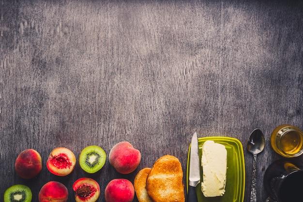 Conceito de pequeno-almoço saudável. torradas com manteiga, mel, frutas e chá sobre fundo escuro de madeira. vista do topo. copie o espaço. ainda vida. postura plana. tonificado