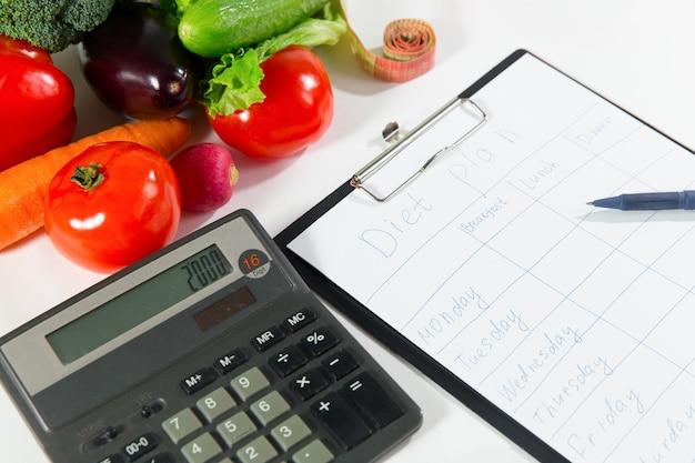 Conceito de perda de peso, alimentos orgânicos saudáveis. composição vegetal, fita métrica, calculadora e caderno com plano de dieta isolado no fundo branco, vista de perto