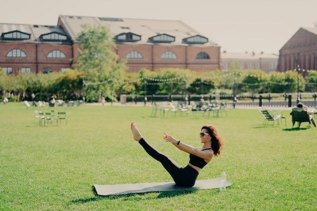 Conceito de perda de peso e fitness de pilates. mulher jovem morena positiva tem treinamento ao ar livre levanta poses de pernas no treino regular de karemathas usa roupas esportivas, óculos de sol, alonga os músculos.