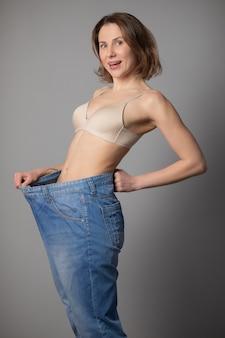 Conceito de perda de peso. jovem mostra sua perda de peso e vestindo seus jeans velhos. mulher magro em jeans grandes mostrando como ela estava perdendo peso