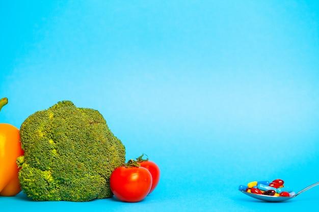 Conceito de perda de peso, uma escolha entre colher de comprimidos ou legumes frescos