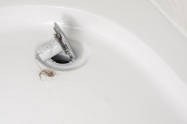 Conceito de perda ou alopecia de cabelo. tamancos no chuveiro após a lavagem. feche acima, copie o espaço.