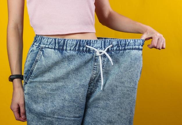 Conceito de perder peso. mulher em jeans muito grandes em um fundo amarelo do estúdio. cortar foto