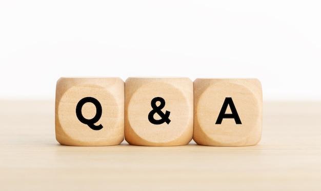 Conceito de perguntas e respostas ou perguntas e respostas. blocos de madeira com texto na mesa. copie o espaço