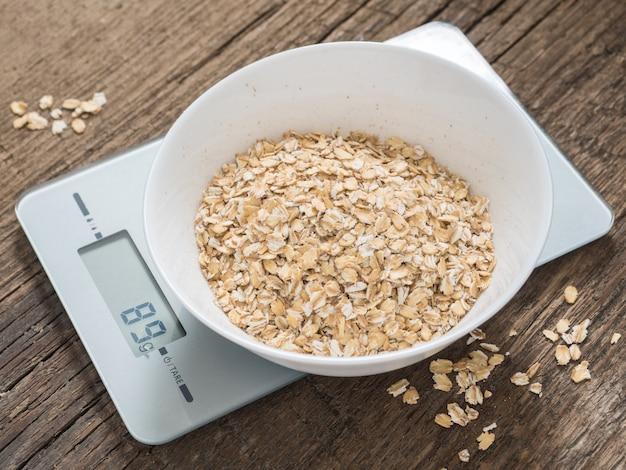 Conceito de pesagem do produto. mingau de aveia em uma tigela branca na balança da cozinha no fundo de madeira