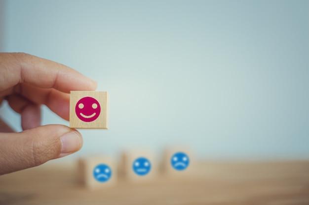Conceito de pesquisa de satisfação: mão escolhe um rosto sorridente no cubo de bloco de madeira. descreve os melhores serviços empresariais excelentes que classificam a experiência do cliente.