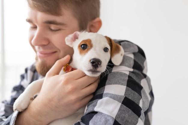 Conceito de pessoas, animais de estimação e animais - close-up de jovem segurando o cachorrinho jack russell terrier