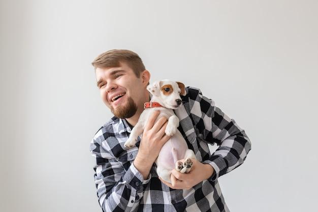 Conceito de pessoas, animais de estimação e animais - homem bonito segurando o cachorrinho jack russell terrier.