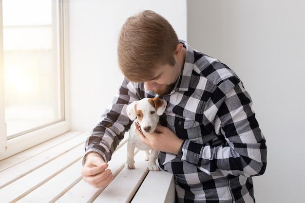 Conceito de pessoas, animais de estimação e animais - jovem abraçando jack russell terrier cachorrinho perto de janela em fundo branco.