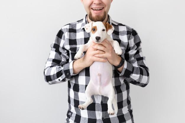 Conceito de pessoas, animais de estimação e cães - close-up do homem abraçando um cachorrinho engraçado no fundo branco