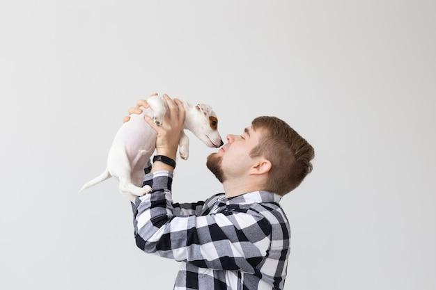 Conceito de pessoas, animais de estimação e cães - jovem abraçando um cachorrinho engraçado no fundo branco