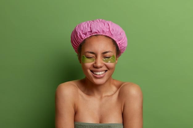 Conceito de pessoas, beleza e higiene. mulher afro-americana alegre usa touca de banho, enrolada em uma toalha, aplica-se sob o tapa-olho após tomar banho, se preocupa com a pele, posa contra a parede verde