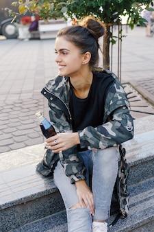 Conceito de pessoas, beleza, moda, estilo de vida e cor - retrato de corpo inteiro ao ar livre da bela jovem sorridente feliz posando na rua. modelo olhando para a câmera. senhora vestindo roupas elegantes