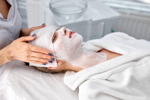 Conceito de pessoas, beleza, spa, cosmetologia e cuidados com a pele. bela jovem deitada com os olhos fechados enquanto o cosmetologista aplica a máscara facial e a máscara de pano na sala de cosmetologia do spa. copie o espaço