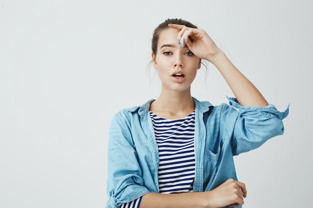 Conceito de pessoas bonitas. foto de estúdio de concurso mulher bonita com roupa da moda, segurando a mão na testa e de pé com a boca aberta, expressando sensualidade