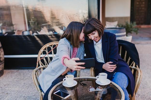 Conceito de pessoas, comunicação e amizade - jovens mulheres sorridentes bebendo café ou chá e conversando no café no terraço ao ar livre e tomando uma selfie com telefone móvel