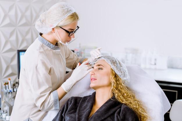 Conceito de pessoas, cosmetologia, cirurgia plástica, antienvelhecimento e beleza - mulher jovem e bonita e médica cosmetologista, fazendo a injeção de elevação na testa, sala clínica moderna