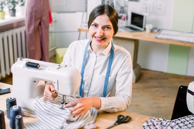 Conceito de pessoas, costureira, alfaiate e moda - jovem designer de moda em seu showroom usando a máquina de costura