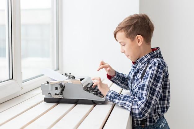 Conceito de pessoas, crianças e estilo - menino com uma velha máquina de escrever preta na superfície branca