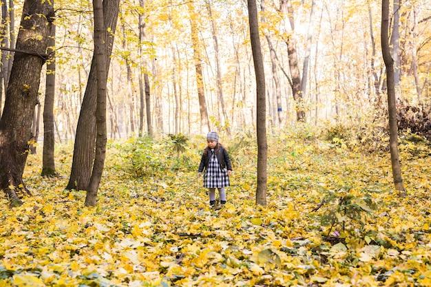 Conceito de pessoas, crianças e natureza. menina sorridente no parque outono.