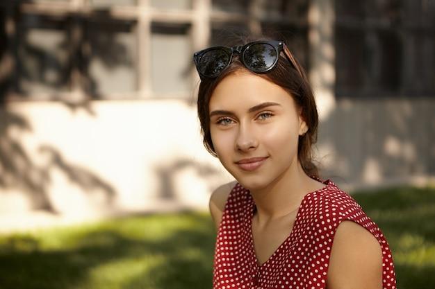Conceito de pessoas, descanso, beleza, estilo e moda. retrato de uma linda jovem caucasiana encantadora com óculos de sol na cabeça, aproveitando o belo dia de verão ao ar livre