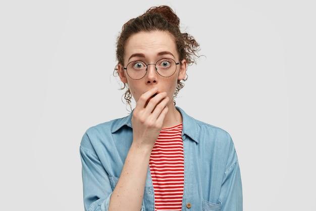 Conceito de pessoas e admiração. jovem fêmea sardenta atordoada com olhar assustado, mantém a mão na boca, fofoca com amigos, suspira de medo e espanto, usa óculos redondos, camisa casual